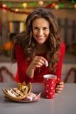 Frau, die eine Schale heiße Schokolade und Weihnachtsbonbons isst stockfotografie