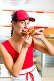 Frau, die eine Scheibe der Pizza isst Stockbilder