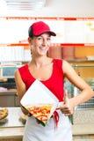 Frau, die eine Scheibe der Pizza isst Lizenzfreie Stockfotos