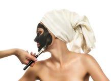 Frau, die eine Schlammmaske auf dem weißen Hintergrund empfängt. Lizenzfreie Stockfotos