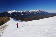 Frau, die eine steile Schneesteigung klettert lizenzfreies stockfoto