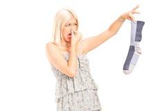 Frau, die eine stinky Socke hält lizenzfreies stockfoto