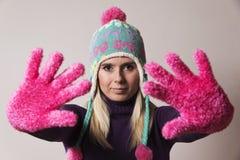 Frau, die eine Strickmütze ausdehnt ihre Hände vor ihr trägt Lizenzfreie Stockfotografie