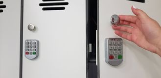 Frau, die eine Tür des weißen Schließfachs der Sicherheit mit elektrischen Codeverschlüssen öffnet stockbild