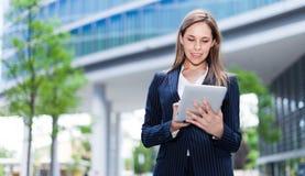 Frau, die eine Tablette verwendet lizenzfreies stockbild