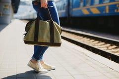 Frau, die eine Tasche an einem Bahnhof hält stockfoto