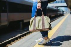 Frau, die eine Tasche an einer Bahnstation hält stockfotos