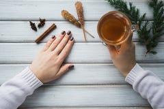 Frau, die eine Tasse Tee über dem Holztisch hält Stockfotos