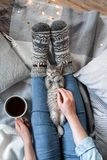 Frau, die eine Tasse Tee beim Spielen mit ihrer Katze hält stockfotos