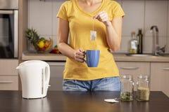 Frau, die eine Tasse Tee herstellt lizenzfreie stockfotografie