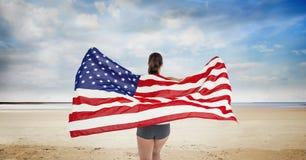 Frau, die eine USA-Flagge im Strand hält Stockfotos