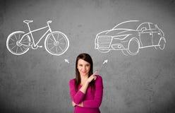 Frau, die eine Wahl zwischen Fahrrad und Auto trifft Stockfotografie