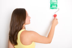 Frau, die eine Wand malt stockbild