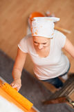 Frau, die eine Wand mit Farbenrolle malt Stockfotos