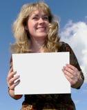 Frau, die eine weiße Karte anhält Lizenzfreie Stockfotos