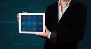 Frau, die eine weiße Tablette mit undeutlichen apps hält Lizenzfreies Stockfoto