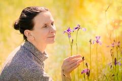 Frau, die eine wilde Iris sibirica Blume schaut Stockbilder