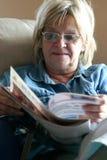 Frau, die eine Zeitschrift liest Stockbild