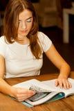 Frau, die eine Zeitschrift zur Teezeit liest Lizenzfreies Stockfoto
