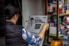 Frau, die eine Zeitung Hanoi liest lizenzfreie stockfotografie