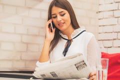 Frau, die eine Zeitung liest und am Handy spricht lizenzfreies stockbild