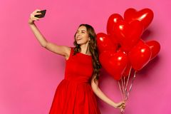 Frau, die eine Zunge beim Nehmen von selfie mit roten Ballonen blinzelt und zeigt Lizenzfreie Stockfotos