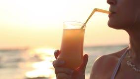 Frau, die an einem Auffrischungscocktail bei Sonnenuntergang nippt stock video footage