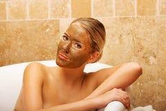Frau, die in einem Bad mit Gesichtsmaske sitzt Lizenzfreies Stockfoto