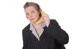 Frau, die an einem Bananentelefon spricht Stockfoto