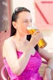 Frau, die in einem Biergarten trinkt Lizenzfreie Stockbilder