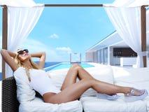 Frau, die in einem Cabana am Pool sich entspannt Wiedergabe 3d lizenzfreies stockfoto