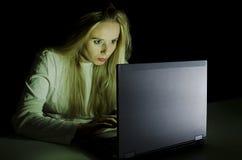 Frau, die an einem Computer bis zum der Nacht horizontal arbeitet Stockfotos