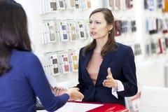 Frau, die in einem Elektronikspeicher sich beschwert Lizenzfreie Stockfotos