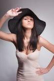 Frau, die in einem Hut aufwirft stockfoto