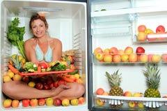 Frau, die in einem Kühlraum sitzt Stockbild