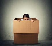 Frau, die in einem Kartonkasten sich versteckt Stockbilder