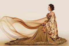 Frau, die in einem Kleid sitzt Lizenzfreies Stockfoto