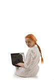 Frau, die an einem Laptop arbeitet Stockbild