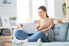 Frau, die an einem Laptop arbeitet lizenzfreies stockbild