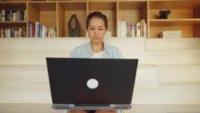 Frau, die an einem Laptop beim Sitzen arbeitet stock video