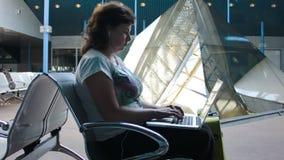 Frau, die an einem Laptop am Flughafen arbeitet stock video