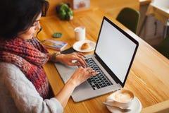 Frau, die an einem Laptop im Café arbeitet lizenzfreies stockbild