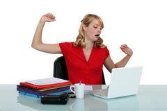 Frau, die an einem Laptop sitzt Stockbild