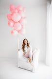 Frau, die in einem Lehnsessel sitzt und ein Bündel rosa Ballone hält Lizenzfreie Stockfotografie