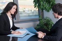Frau, die an einem Mann im Büro lächelt Lizenzfreie Stockbilder