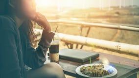 Frau, die in einem Naturpark unter Verwendung eines Notizbuches arbeitet In einem Kaffee Lizenzfreie Stockfotos