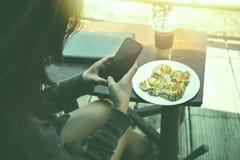 Frau, die in einem Naturpark unter Verwendung eines Notizbuches arbeitet In einem Kaffee Stockfoto
