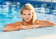 Frau, die in einem Pool sich entspannt Lizenzfreie Stockbilder