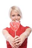 Frau, die einem roten Herzen geformten Lutscher darstellt Lizenzfreie Stockfotografie