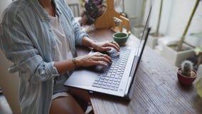 Frau, die an einem Schreibtisch mit ihrer Laptopfunktion sitzt stock video footage